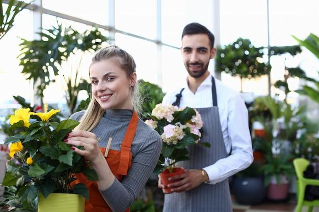 Lächelnder florist holding blooming flowers im topf