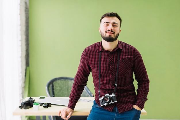 Lächelnder fotograf posiert