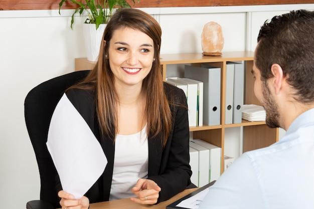 Lächelnder frauengeschäftsführer, der mit wichtigem mannkunden im büro spricht