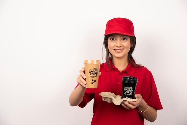 Lächelnder frauenkurier, der kaffee für lieferung auf weißem hintergrund hält.