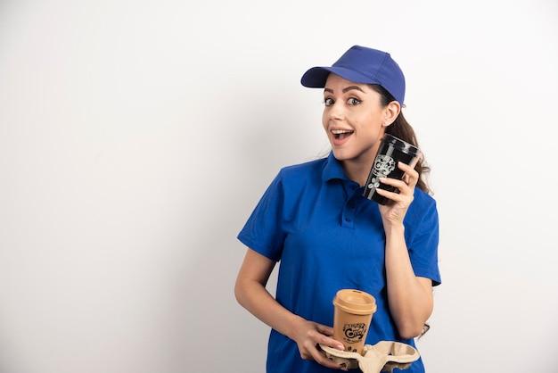 Lächelnder frauenkurier mit zwei tassen kaffee. foto in hoher qualität