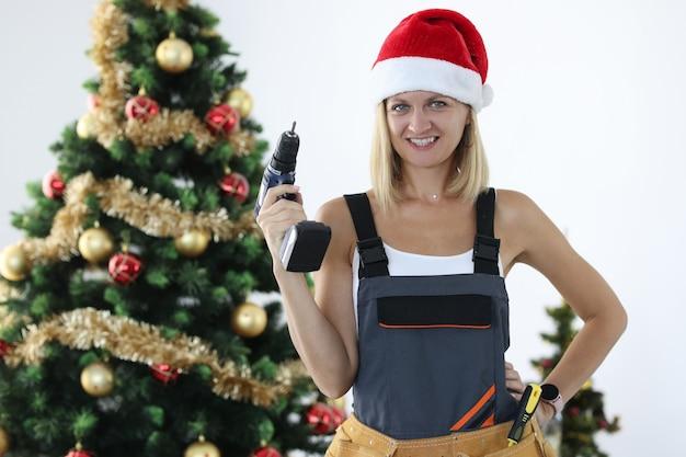 Lächelnder frauenmechaniker in uniform und weihnachtsmann-hut, der bohrer in den händen nahe weihnachtsbaum hält. weihnachtsrabatte und werbeaktionen für das reparaturservice-konzept
