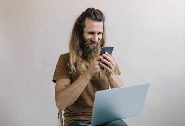 Lächelnder freiberufler mit laptop, handy, von zu hause aus arbeiten. bärtiger mann, der essen online bestellt