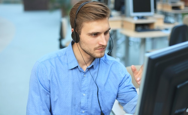 Lächelnder freundlicher, gutaussehender junger männlicher callcenter-betreiber
