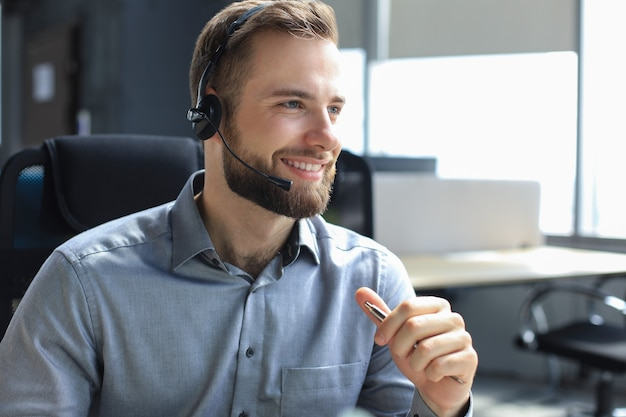 Lächelnder freundlicher hübscher junger männlicher call-center-betreiber. Premium Fotos