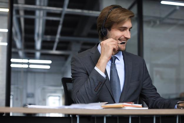 Lächelnder freundlicher hübscher junger männlicher call-center-betreiber.
