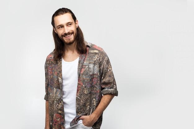 Lächelnder freundlicher lustiger kerl, attraktiver und freundlicher hippie. stilvoller sorgloser mann des hipster-reisenden auf einem weißen studiohintergrund, menschenlebensstil