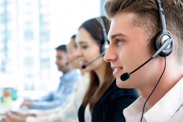 Lächelnder freundlicher mann, der im call-center-büro mit team arbeitet