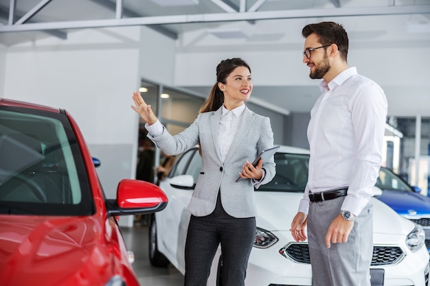 Lächelnder freundlicher weiblicher autoverkäufer mit tablette in den händen, die mit einem mann, der ein auto kaufen will, über autospezifikationen sprechen. innenraum des autosalons.
