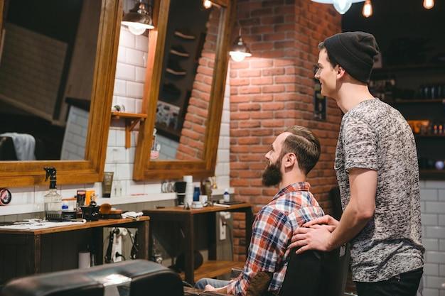 Lächelnder friseur und zufriedener mann mit bart und neuem haarschnitt im spiegel