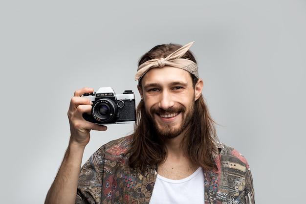 Lächelnder fröhlicher glücklicher hipster-fotograf mit einer kamera in seinen händen fotografiert auf einer filmkamera, stilvoll gekleidet in einem hippie-stil, kreative person auf einem weißen studiohintergrund