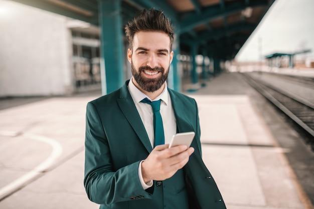 Lächelnder fröhlicher kaukasischer bärtiger kaukasischer geschäftsmann, der smartphone benutzt und auf zug wartet. folge deinen träumen sie kennen den weg.
