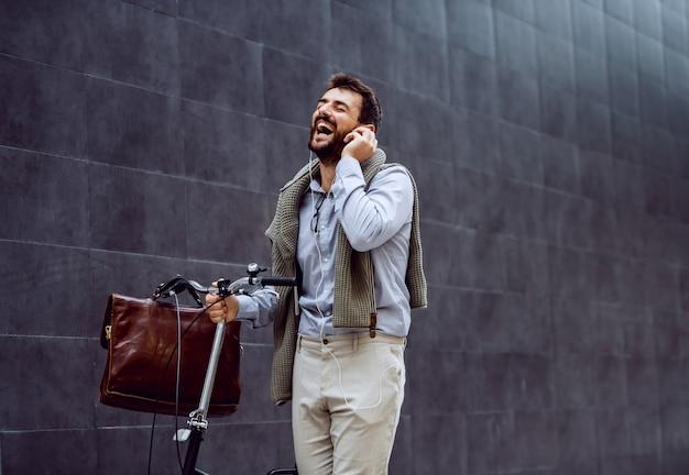 Lächelnder fröhlicher kaukasischer modischer geschäftsmann, der musik hört und sein fahrrad schiebt. im hintergrund ist graue wand.