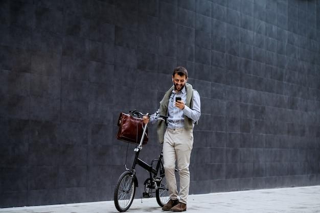 Lächelnder fröhlicher kaukasischer modischer geschäftsmann, der smartphone benutzt und sein fahrrad schiebt. im hintergrund ist graue wand.