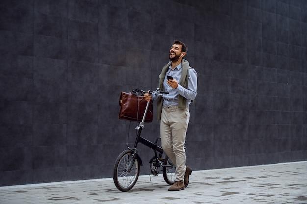 Lächelnder fröhlicher kaukasischer modischer geschäftsmann, der smartphone hält, musik hört und sein fahrrad schiebt. im hintergrund ist graue wand.
