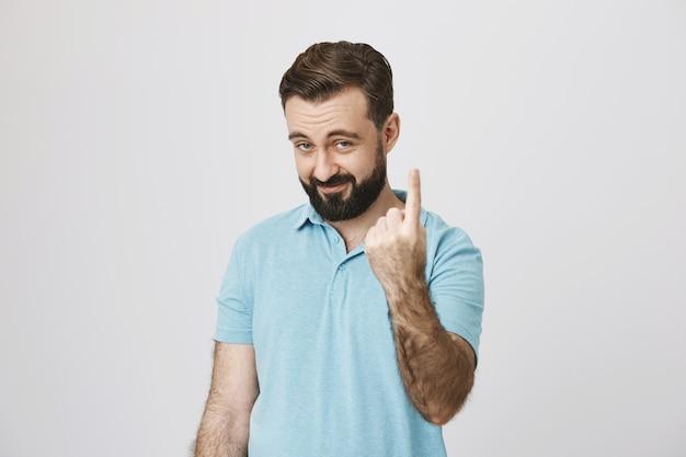 Lächelnder fröhlicher kerl, der finger zeigt, nummer eins