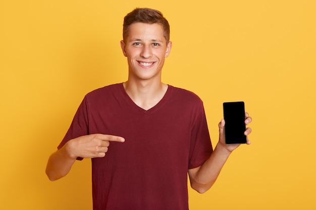 Lächelnder fröhlicher kerl, der telefon mit leerem bildschirm hält