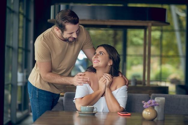Lächelnder fürsorglicher mann, der schultern der freudigen frau mit langen haaren umarmt, die am tisch im café sitzen