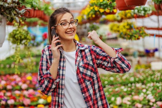 Lächelnder gärtner, der im gewächshaus steht und bestellungen von einem kunden über smartphone entgegennimmt.