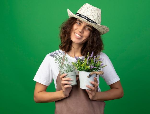 Lächelnder gärtner der jungen frau in der uniform, die gartenhut hält, der blumen in den blumentöpfen hält, die auf grün lokalisiert werden