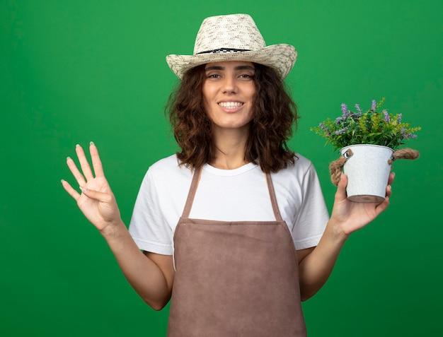Lächelnder gärtner der jungen frau in uniform, die gartenhut hält, der blume im blumentopf hält, der vier lokalisiert auf grün zeigt