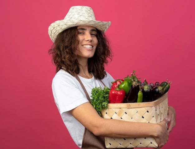 Lächelnder gärtner der jungen frau in uniform, die gartenhut hält, der gemüsekorb lokalisiert auf rosa hält