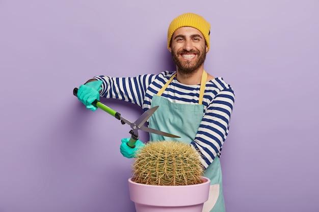 Lächelnder gärtner, der mit einem großen topfkaktus aufwirft