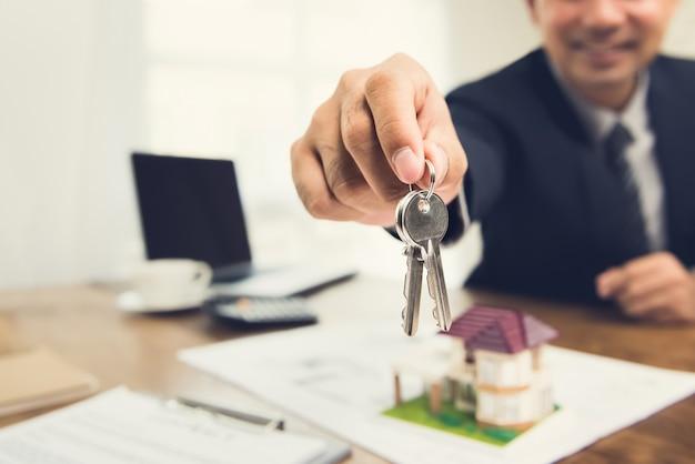 Lächelnder geschäftsmann als immobilienmakleragent, der hausschlüssel gibt