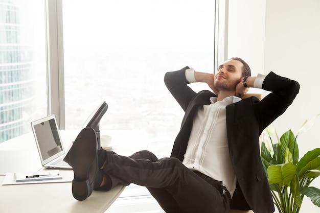 Lächelnder geschäftsmann, der am arbeitsplatz im modernen büro sich entspannt.