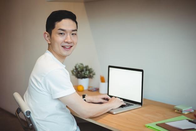 Lächelnder geschäftsmann, der am laptop arbeitet