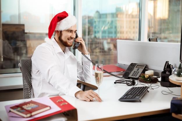 Lächelnder geschäftsmann, der am telefon am worplace-weihnachtstag spricht.