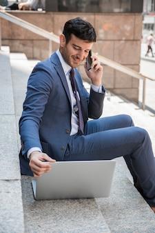 Lächelnder geschäftsmann, der am telefon spricht und laptop durchstöbert