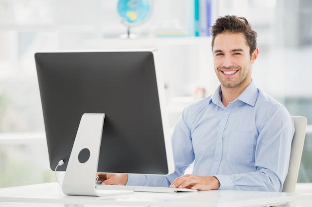 Lächelnder geschäftsmann, der an computer arbeitet