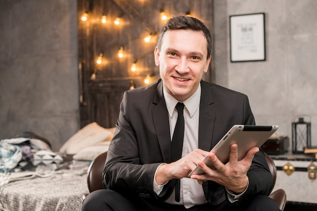 Lächelnder geschäftsmann, der an tablette arbeitet