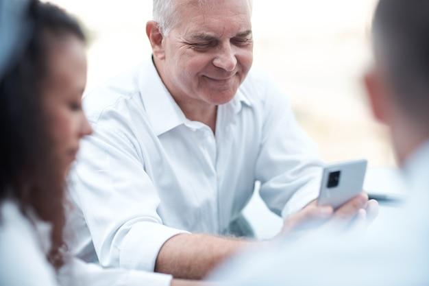 Lächelnder geschäftsmann, der auf den bildschirm seines smartphones schaut