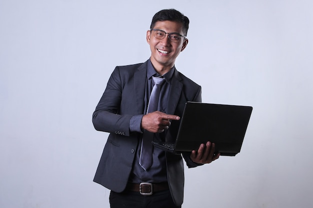 Lächelnder geschäftsmann, der auf einen laptop zeigt