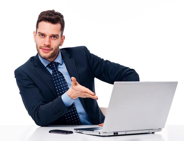 Lächelnder geschäftsmann, der auf laptop zeigt