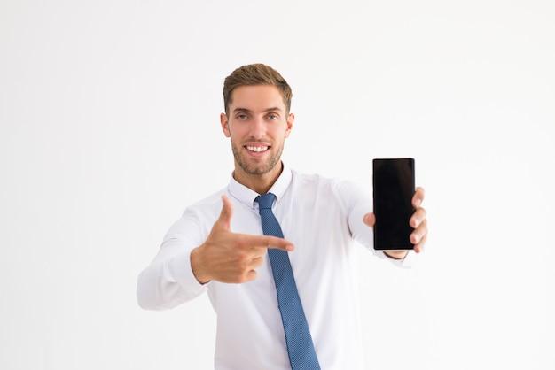 Lächelnder geschäftsmann, der auf smartphone zeigt