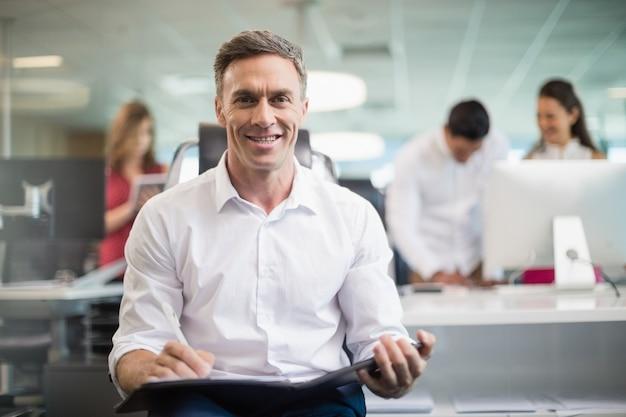 Lächelnder geschäftsmann, der auf stuhl sitzt und auf zwischenablage im büro schreibt