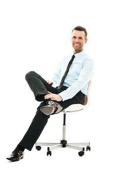 Lächelnder geschäftsmann, der auf stuhl sitzt