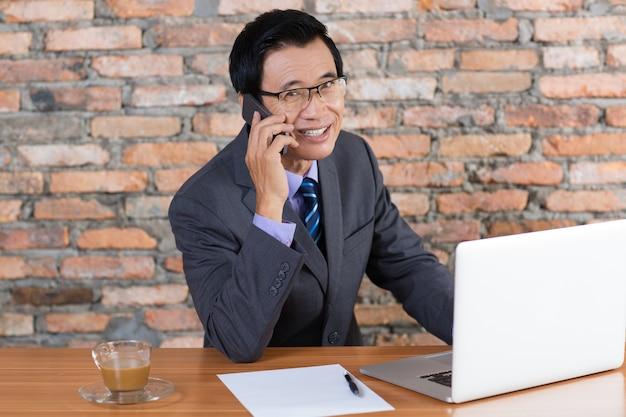 Lächelnder geschäftsmann, der auf telefon am schreibtisch