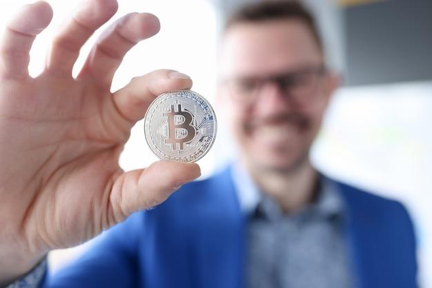 Lächelnder geschäftsmann, der bitcoin hält, das geld mit bitcoins ohne investitionen verdient