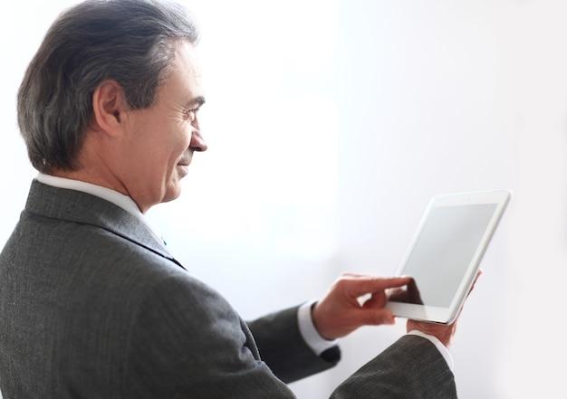 Lächelnder geschäftsmann, der den bildschirm des digitalen tabletts tippt.