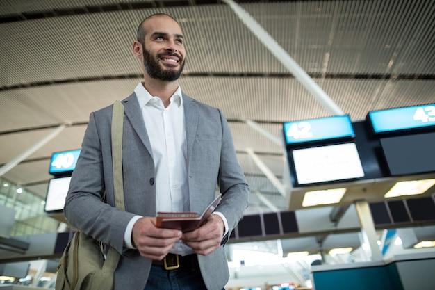 Lächelnder geschäftsmann, der eine bordkarte und einen reisepass hält