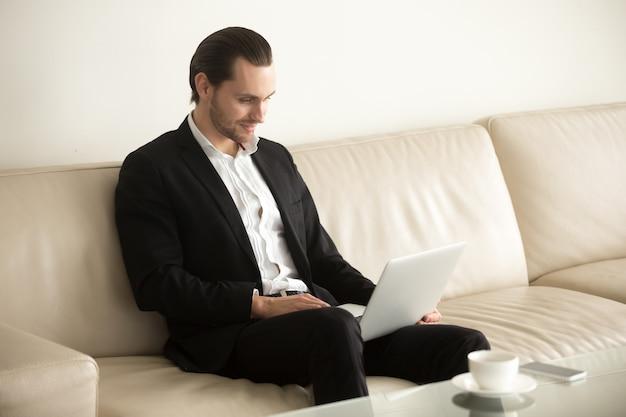 Lächelnder geschäftsmann, der entfernt an laptop von zu hause aus arbeitet.