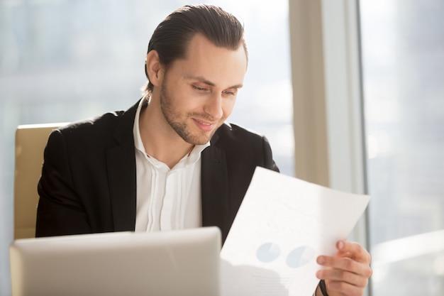 Lächelnder geschäftsmann, der finanzbericht betrachtet