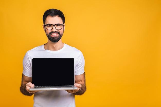 Lächelnder geschäftsmann, der finger auf leerem laptopbildschirm lokalisiert über gelbem hintergrund zeigt. kamera betrachten.