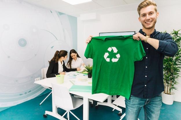 Lächelnder geschäftsmann, der grünes t-shirt mit recycling-symbol zeigt