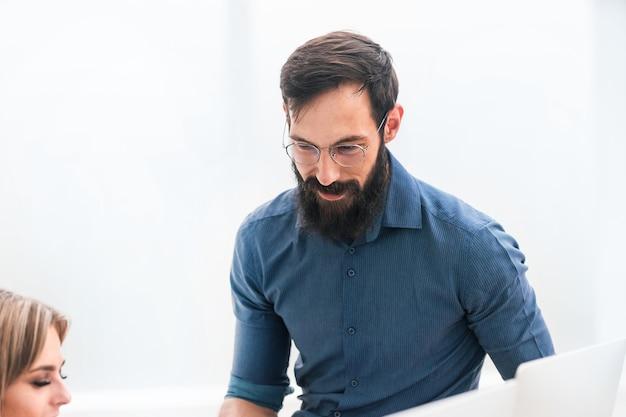 Lächelnder geschäftsmann, der im büro arbeitet. foto mit kopierraum