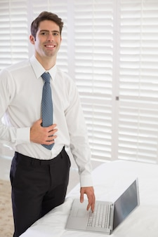 Lächelnder geschäftsmann, der laptop am hotelzimmer verwendet